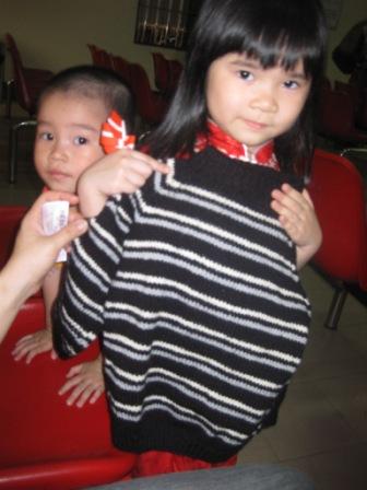 Et barn får en trøje i ventesal